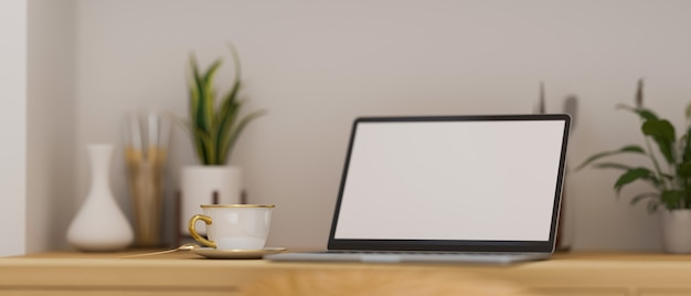 Computer portatile moderno con mockup schermo vuoto su tavolo da lavoro in legno con decorazione moderna 3d