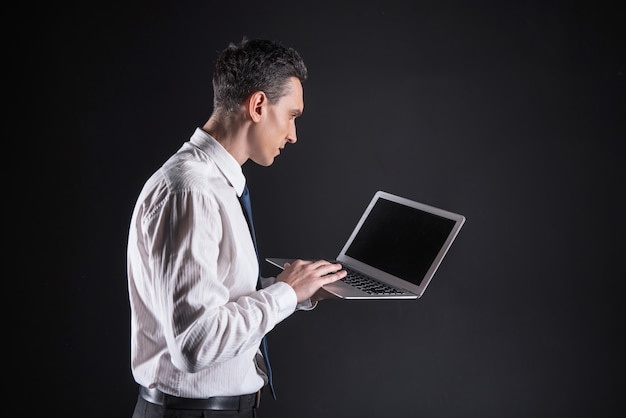 Computer portatile moderno. uomo adulto intelligente serio che tiene un laptop e guarda il suo schermo mentre utilizza questo dispositivo per lavoro