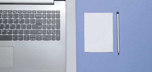 Computer portatile moderno e foglio di carta bianca per copia spazio su sfondo blu grigio. vista dall'alto.