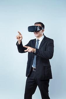 Moderna attività per il tempo libero. immagine ritagliata di un gentiluomo maturo emotivo che gesticola mentre si eccita durante un gioco di realtà visiva.