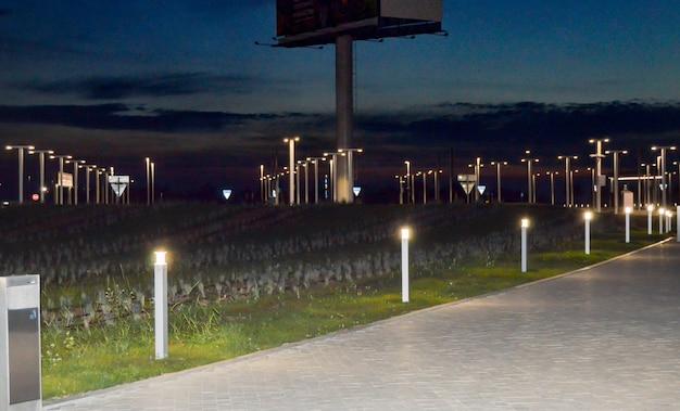 Sistema di illuminazione moderno nella città notturna, lanterne lungo la strada.