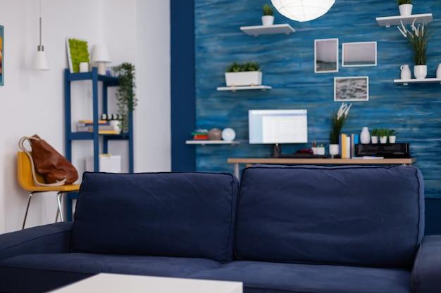 Soggiorno moderno senza nessuno con mobili e pareti blu, splendidamente decorato. arredamento abbastanza semplice dell'appartamento. elegante decorazione retrò, accogliente.