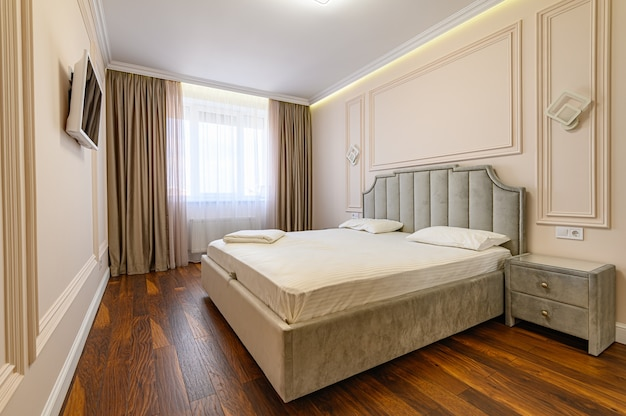 Interno camera da letto di lusso moderno con letto matrimoniale nei colori beige e marroni