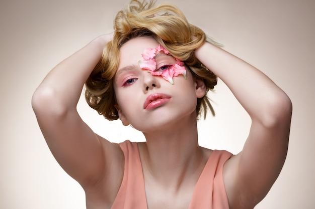Per la rivista moderna. modello tenero con ombretti rosa in posa per una rivista moderna con petali sul viso