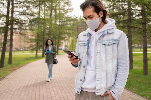 Uomo moderno in giacca di jeans e maschera facciale in piedi nel parco e controllando il messaggio telefonico