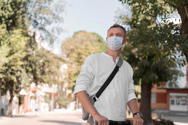 Uomo moderno su scooter che indossa una maschera per il viso