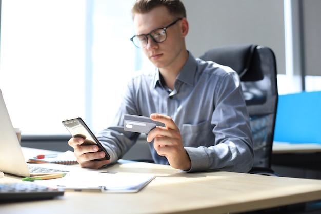 Uomo moderno che utilizza carta di credito e telefono cellulare per il pagamento online. concetto di acquisto mobile.