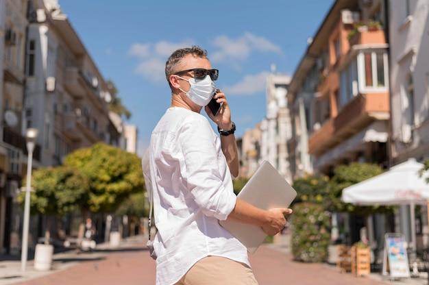 Uomo moderno con mascherina medica parlando al telefono all'esterno
