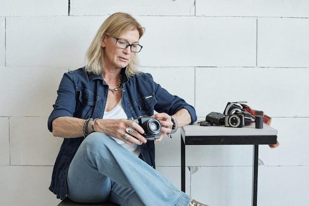 Fotografo moderno della signora matura con capelli biondi che controlla la macchina fotografica prima del servizio fotografico in studio