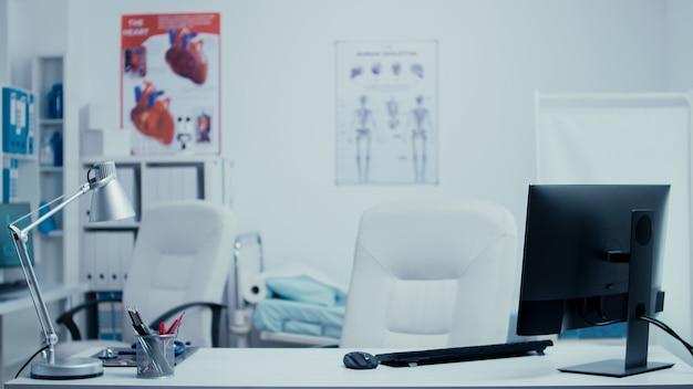 Moderno ufficio di consulenza medica senza nessuno al suo interno. stanza clinica privata dell'ospedale con pareti di vetro, computer sull'armadietto dei medicinali pulito del sistema sanitario della reception. apparecchiature per il trattamento e professio