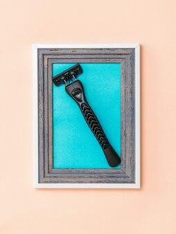 Rasoio da uomo moderno in cornice su fondo corallo. collage. minimalismo. creatività creativa moderna.