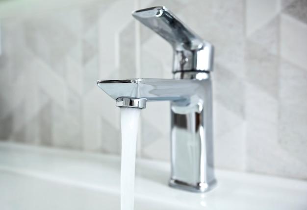 Il moderno rubinetto in metallo nel bagno