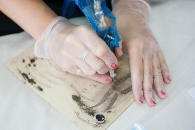 Moderna tecnica di microblading. primo piano della mano femminile dell'estetista usando la macchina del tatuaggio per disegnare le sopracciglia su carta.