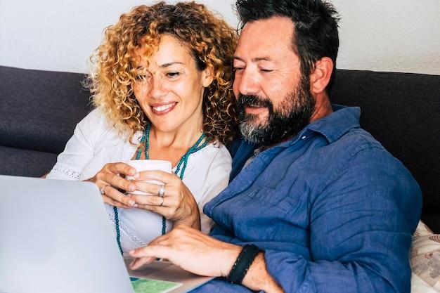 Moderna coppia di 40 anni di mezza età su internet con laptop seduto sul divano di casa durante la ricerca e l'utilizzo della tecnologia web per lavoro o shopping online