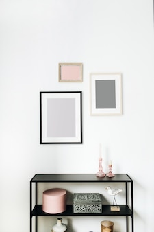 Concetto di interior design nordico scandinavo minimale moderno decorato con cornici per foto, figurine di uccelli, cremagliera su bianco.