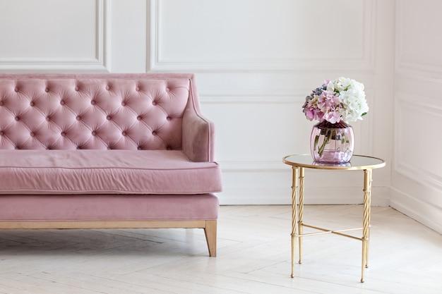 Interno moderno e minimalista del salone con il sofà e il tavolino da salotto rosa con il vaso del mazzo di hortensia dei fiori contro la parete bianca.