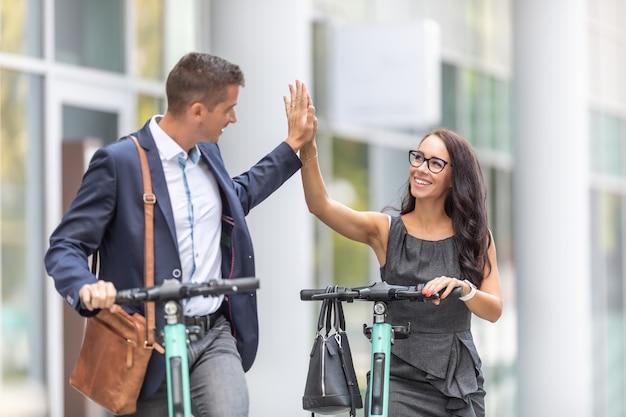 Mobilità moderna ed e-scooter che usano i colleghi che danno il cinque durante i loro spostamenti di lavoro in ufficio.