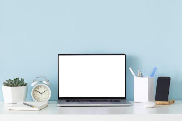 Modello moderno con scrivania da ufficio su sfondo bianco tavolo. posto di lavoro in stile moderno sullo sfondo della parete blu.