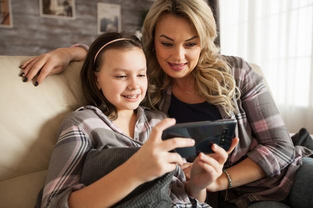 Madre moderna e la sua piccola figlia con bretelle che registrano una chiamata per i nonni.