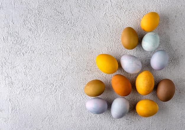 Uova di pasqua colorate naturali moderne. composizione di pasqua su sfondo grigio cemento.