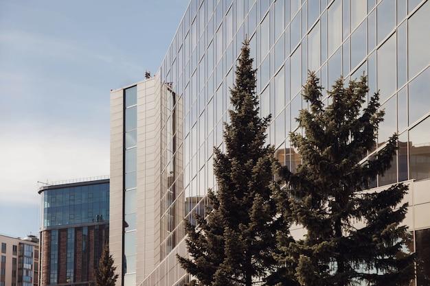 Edificio per uffici moderno con alberi verdi. concetto di business per il settore immobiliare, l'edilizia aziendale e l'ecologia, guardando in alto la vista panoramica dello skyline della città moderna con cielo blu e albero verde. copia spazio