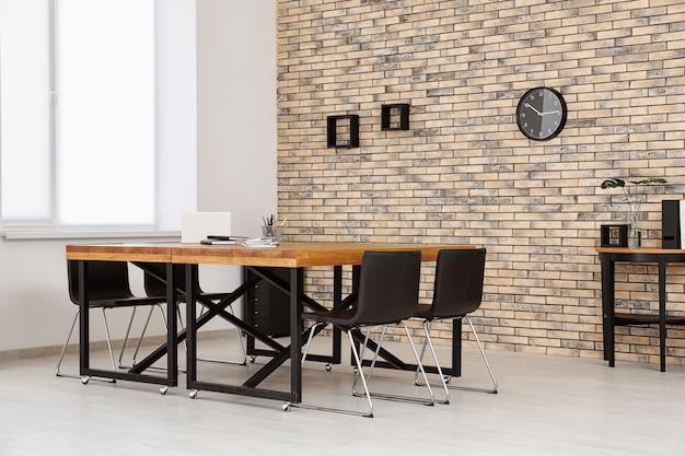 Interiore dell'ufficio moderno con tavoli e sedie in legno