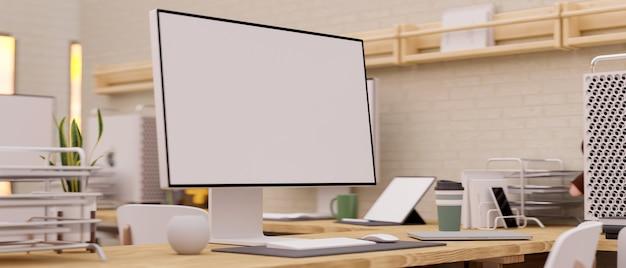 Scrivania moderna del computer del primo piano dello studio dell'ufficio con il modello dello schermo in bianco del computer e le forniture per ufficio