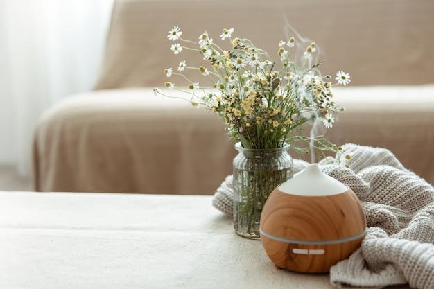 Moderno diffusore di aromi di olio nel soggiorno sul tavolo con elemento a maglia e spazio per la copia di fiori
