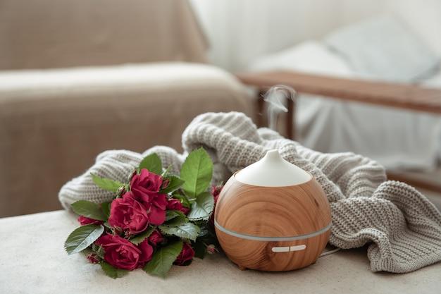 Diffusore di aromi olio moderno nel soggiorno sul tavolo con elemento in maglia e fiori.