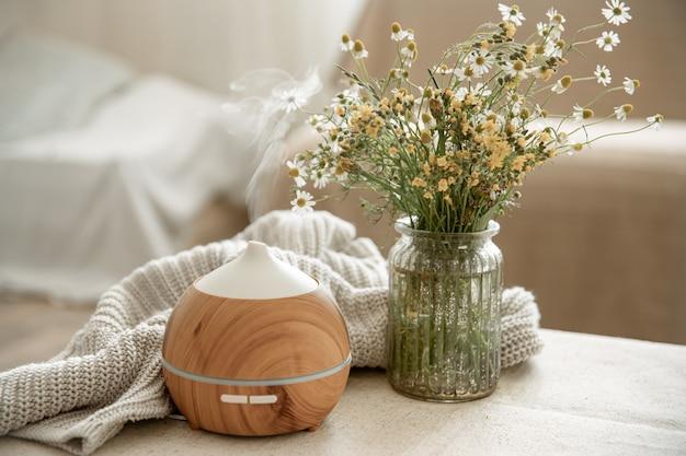 Diffusore di aromi olio moderno nel soggiorno sul tavolo con elemento in maglia e fiori