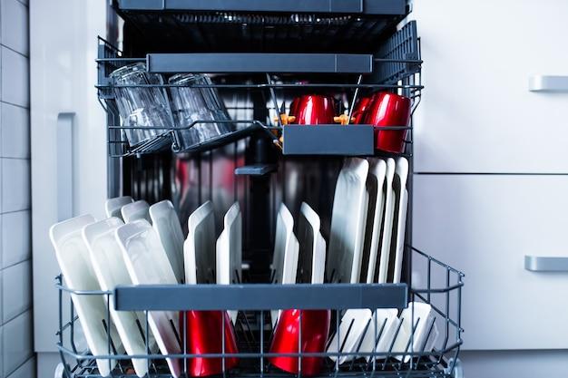 Lavastoviglie aperta moderna con piatti puliti nella cucina bianca.