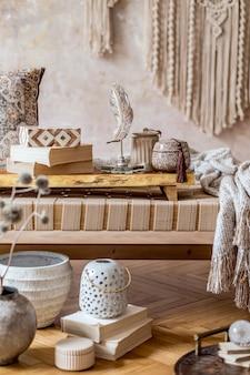 Soggiorno moderno orientale con chaise longue beige di design, bellissimo macramè, cuscini, vassoio in legno, libro, decorazioni ed eleganti accessori personali nell'arredamento della casa.