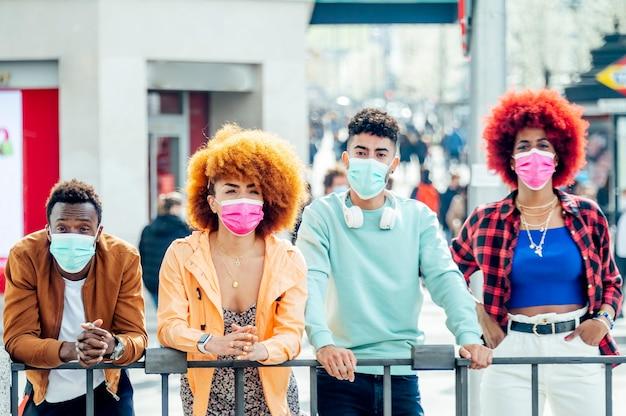 Persone moderne che propongono alla macchina fotografica con maschere facciali