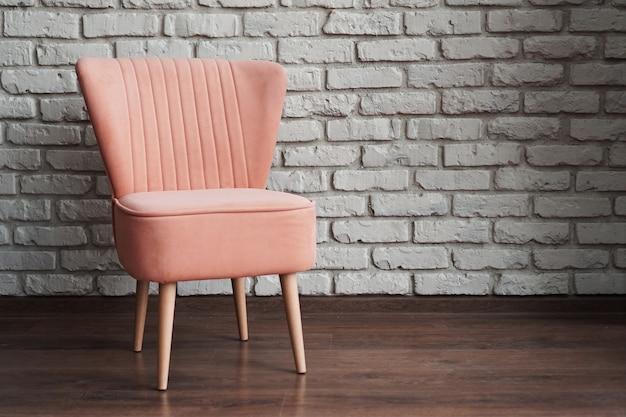 Moderna sedia morbida rosa contro muro di mattoni bianchi e laminato marrone in studio fotografico