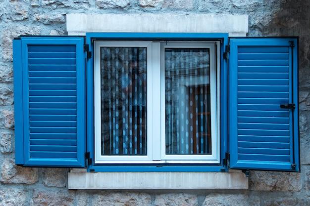 Persiane in plastica moderne sul vecchio edificio, conservazione dello stile dell'architettura con le nuove tecnologie.