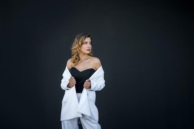 Bella donna moderna in abito bianco isolato su sfondo nero. ritratto femminile.