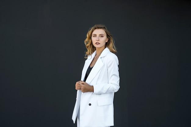 Donna graziosa moderna in vestito bianco isolato