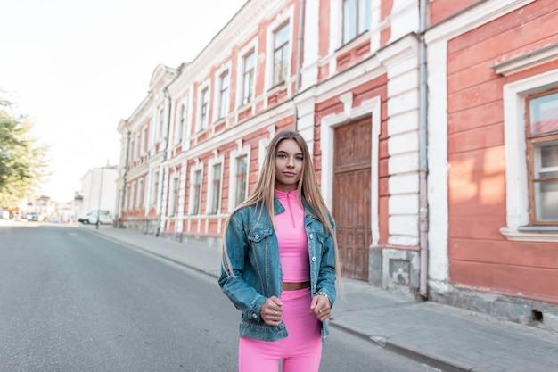 Moderna bella giovane donna bionda con i capelli lunghi in pantaloncini rosa alla moda in un top rosa in una giacca di jeans alla moda si trova sulla strada in città in una giornata estiva. modello di bella ragazza urbana. moda.