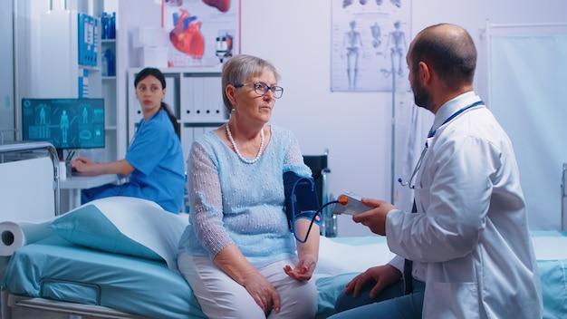 Nei moderni ospedali o cliniche private, l'infermiera scrive i livelli di pressione sanguigna mentre il medico li detta. sistema medico sanitario, trattamento di prevenzione delle malattie, diagnosi delle malattie
