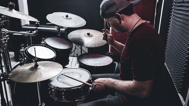 Il batterista professionista moderno suona la batteria in una base di prove, in uno studio di registrazione rosso e nero