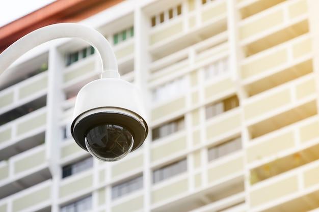 Telecamera cctv pubblica moderna su palo elettrico con sfondo sfocato edificio e spazio di copia.