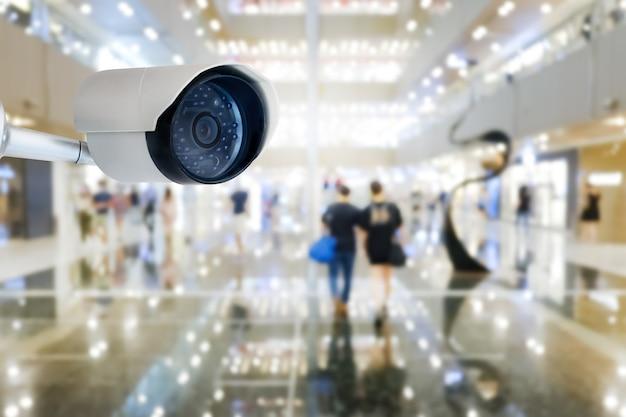 Moderna telecamera cctv pubblica con sfocatura dello sfondo del centro commerciale interno e spazio della copia.