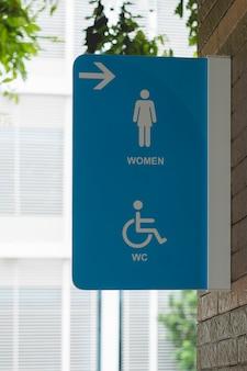 Segno di toilette pubblica moderna sul muro, segni wc donne per bagno.