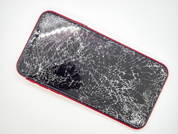 Un moderno smartphone rosso con un display in vetro rotto e un primo piano del corpo curvo danneggiato isolato su superficie bianca