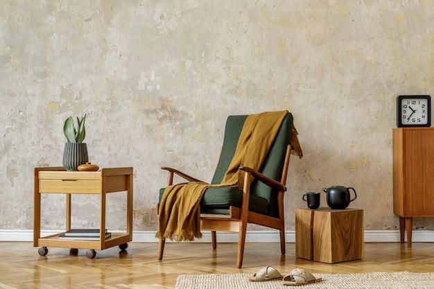 Moderna composizione retrò degli interni del soggiorno con poltrona di design, cubo, teiera, pianta, orologio, comò, plaid, tappeto, decorazione ed eleganti accessori personali nel concetto di wabi sabi.