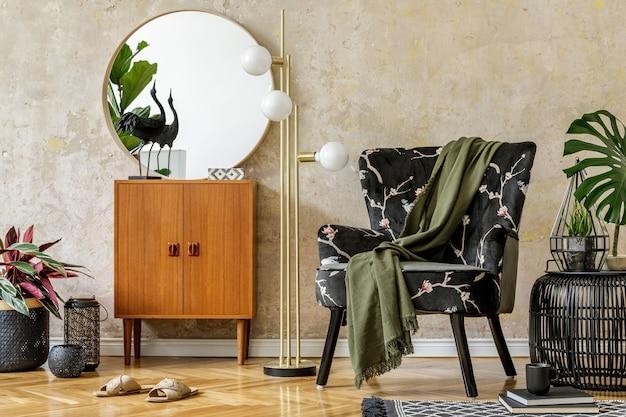 Moderna composizione retrò degli interni del soggiorno con poltrona di design, lampada, pouf in rattan, piante, specchio, decorazione, tappeto ed eleganti accessori personali nel concetto di wabi sabi.