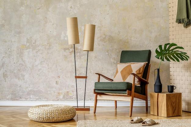 Moderna composizione retrò degli interni del soggiorno con poltrona di design, pouf in rattan, lampada vintage, foglia tropicale, plaid, tappeto, decorazione ed eleganti accessori personali nel concetto di wabi sabi.