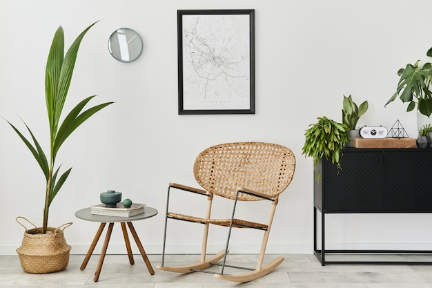 Moderno concetto retrò di interni di casa con poltrona di design in rattan, tavolino da caffè, comò, piante, mappa poster mock up, decorazione e accessori personali. elegante arredamento per la casa del soggiorno.