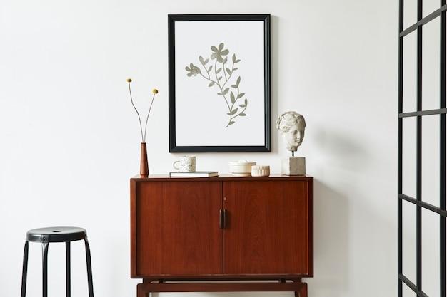 Moderno concetto retrò di interni del soggiorno con comò in teak di design, cornice per poster finta nera, fiori secchi, decorazione, parete bianca e accessori personali. modello.