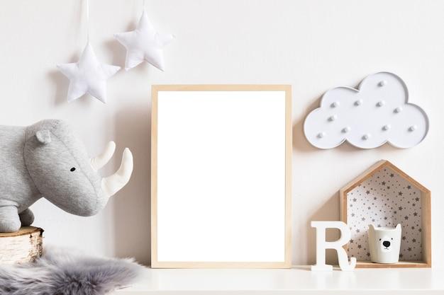 La moderna cameretta scandinava per neonati con cornice per foto, macchinina in legno, giocattoli di peluche e nuvole. bandiere appese in cotone e stelle bianche. interni minimalisti e accoglienti con pareti bianche.
